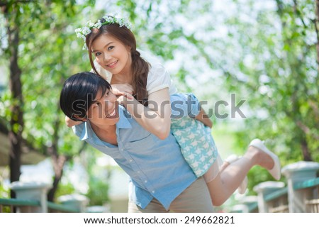 Young asian man giving a piggy back to his girlfriend in the park - stock photo