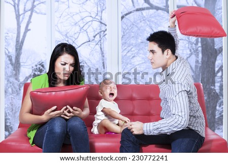 Young asian man hitting his wife near their child and make the child crying - stock photo