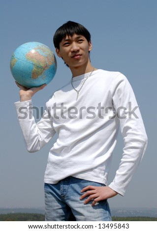 Young Asian man holding a terrestrial globe - stock photo