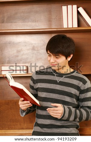 young asian man holding book and smiling - stock photo