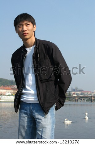 Young Asian man in a black jacket - stock photo