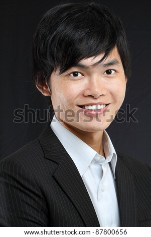 Young asian man in black suit - stock photo