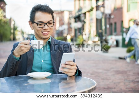 Young asian man in business casual attire sitting and smiling in relaxing outdoor cafe drinking cup of coffee while using mobile phone - stock photo