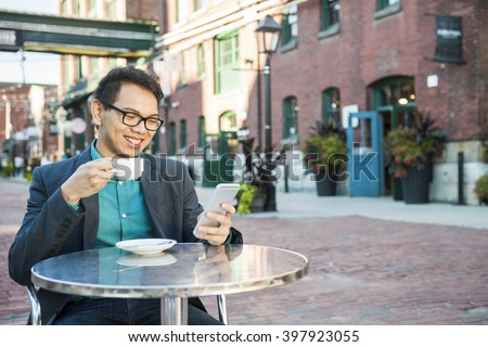 Young asian man in business casual attire sitting and smiling in relaxing outdoor cafe drinking cup of coffee while using mobile phone, with copy space. - stock photo