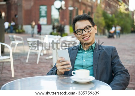 Young asian man in business casual attire sitting and smiling in relaxing outdoor cafe with cup of coffee and mobile phone - stock photo