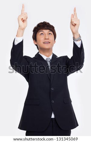 Young asian man indicated up side isolated on white background.