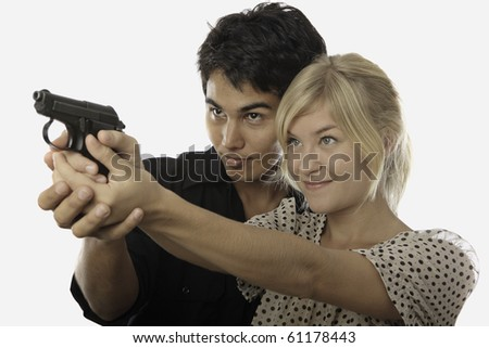 young asian man instructs a young woman about shooting an automatic pistol