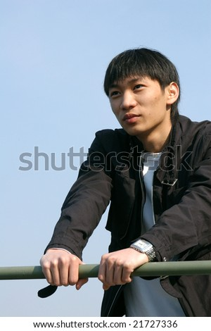 Young Asian man leaning against a barrier - stock photo