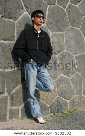 Young Asian man leaning against a stone wall - stock photo