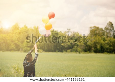 young asian man on green grassland with colored balloons in thailand