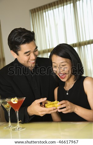 Young Asian man presents a small gift to an attractive Asian woman at a bar. Vertical shot. - stock photo