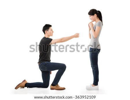 young Asian man propose to his girlfriend, studio shot - stock photo