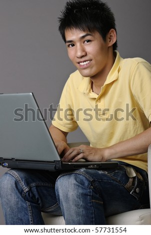 Young Asian man sit on chair and use laptop. - stock photo