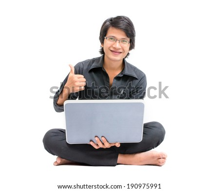 Young asian man sitting on the floor and work with laptop computer