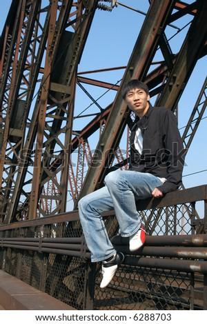 Young Asian man sitting on the railway bridge - stock photo