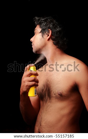 Young Asian man spraying deodorant - stock photo