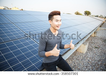 Young asian man standing with a solar panel for renewable energy