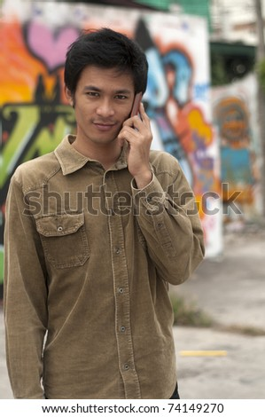 Young Asian man talking on mobile telephone