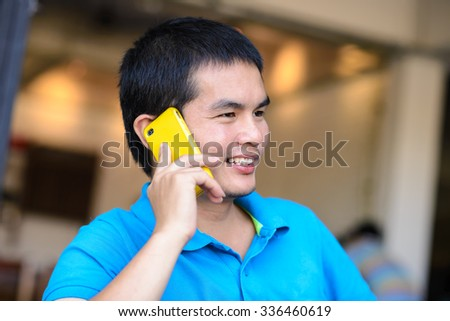 Young Asian man talking on the phone. - stock photo