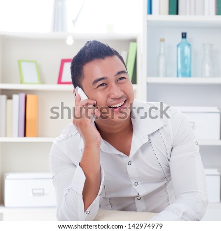 Young Asian man talking on the phone. Lifestyle Southeast Asian man at home. Handsome Asian male model. - stock photo
