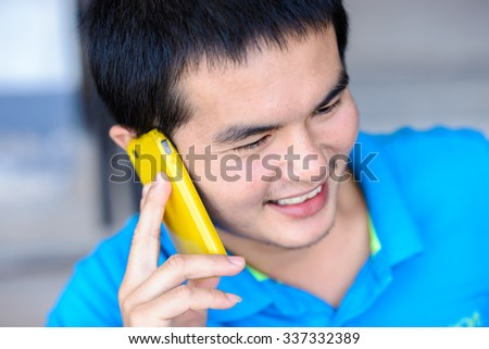 Young Asian man talking on the phone, selective focus on face. - stock photo