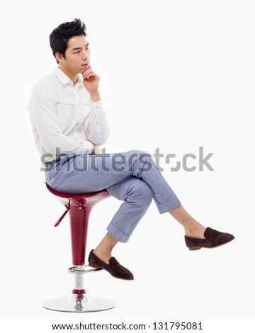 Young Asian man thinking on the chair isolated on white backgroung. - stock photo