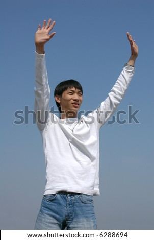 Young Asian man throwing his hands up - stock photo