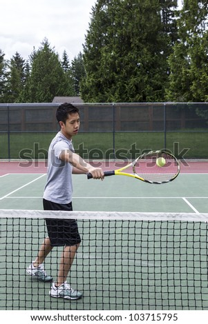 Young Asian Man using backhand volley on outdoor tennis court - stock photo