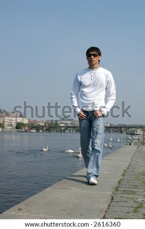 Young Asian man walking along the embankment in Prague, Czech Republic. - stock photo