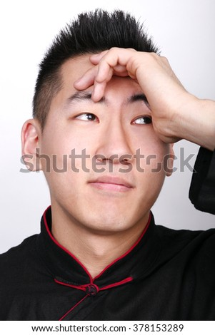 Young Asian man with hand to forehead.