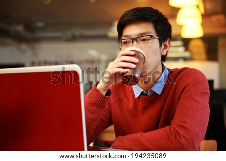 Young asian man working on laptop and drinking coffee - stock photo