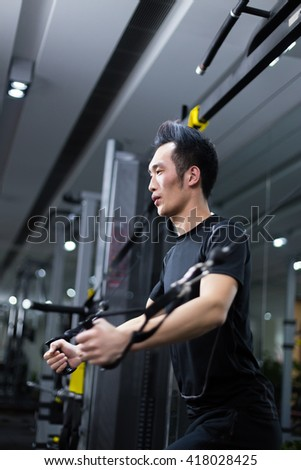 young asian man working out in modern gym