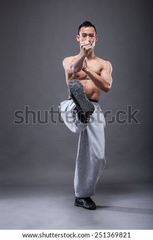 Young asian man workout over grey background karate kick - stock photo