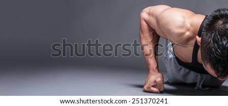 Young asian man workout over grey background with copy-space - stock photo
