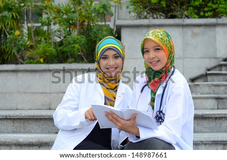 Young asian medical student woman in head scarf smile  - stock photo
