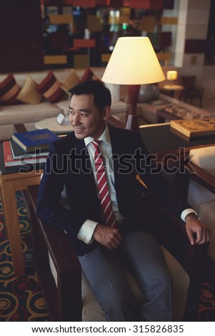 Young asian men entrepreneur dressed in expensive suit sitting in modern luxury space smiling successfully, intelligent managing director relaxing after meeting in armchair of his private office room - stock photo
