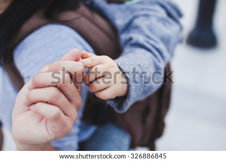 Young asian mother and her son relaxing outdoors. Mother holds her son's finger. Son sitting in sling on mothers back - stock photo