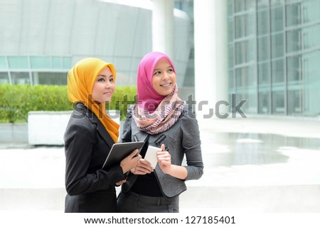Young asian muslim businesswoman in head scarf smile with mobile phone and mobile laptop - stock photo