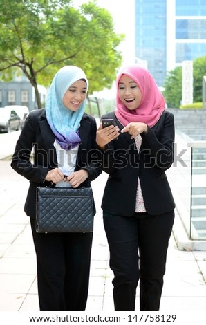 Young asian muslim businesswomen in head scarf smile while walking  - stock photo