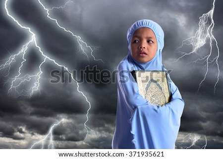 Young Asian Muslim girl in blue hijab hold Al Quran. Conceptual of religion. - stock photo