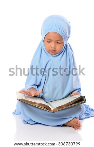 Young Asian Muslim girl in blue hijab reading Al Quran with white background - stock photo