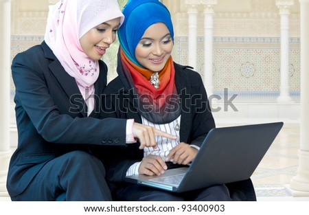 Young Asian muslim girls discuss with laptop - stock photo