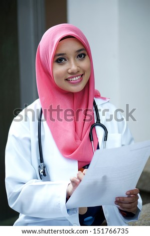 Young asian muslim woman doctor in head scarf smile while holding medical report - stock photo