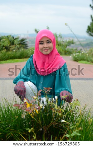Young asian muslim woman happy nursery worker trimming plants  - stock photo