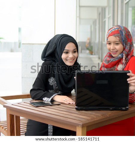 Young asian muslim woman in head scarf discuss and sharing info - stock photo