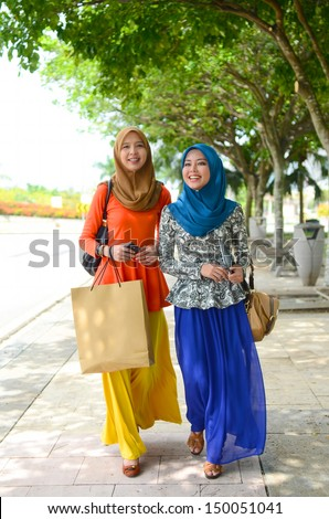 Young asian muslim woman in head scarf happy walking after shopping - stock photo