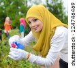 Young asian muslim woman in head scarf nursery trimming plants - stock photo