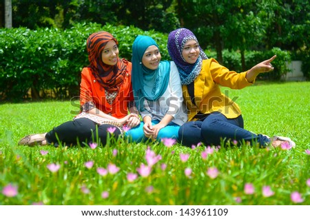 Young asian muslim woman in head scarf smile at garden - stock photo