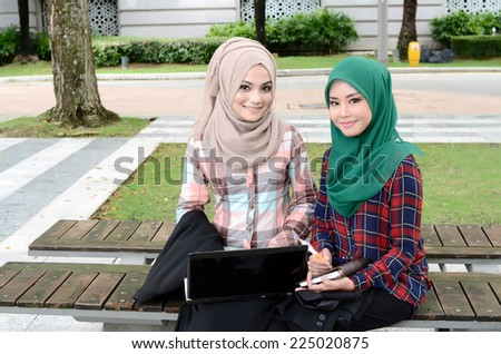 Young asian muslim woman in head scarf smile at park together - stock photo