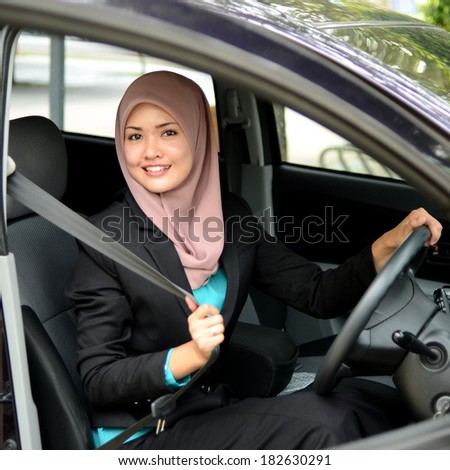 Young asian muslim woman in head scarf smile inside the car - stock photo